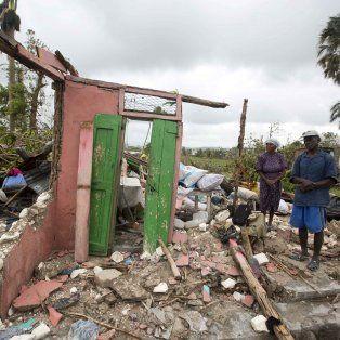 Un ciudadano haitiano y su esposa miran resignados los restos de lo que fue su vivienda.