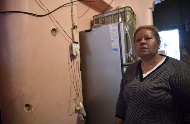 Liliana en el comedor de su casa y ante las perforaciones que los balazos 9 milímetros dejaron en la pared.