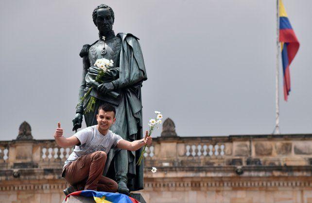 Espaldarazo. Un joven bogotano celebra el galardón noruego subido a la estatua de Simón Bolívar.