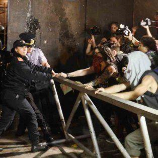 Forcejeos. Un grupo de manifestantes disputa con efectivos policiales mientras intentan correr una de las barandas colocadas sobre uno de los extremos de la iglesia catedral.