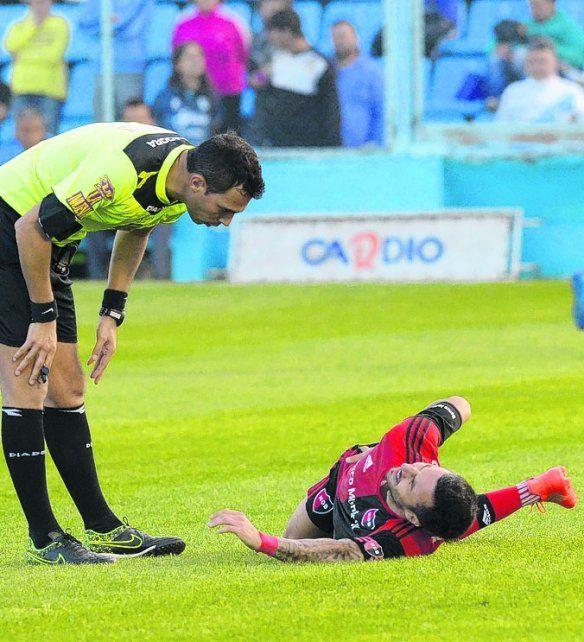 Dolor insoportable. Nacho Scocco quedó tendido en el juego ante Temperley. Se le acercó el juez Facundo Tello.