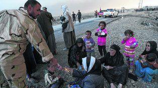 A salvo. Militares iraquíes entregan agua a un grupo de mujeres y chicos que pudo salir de Mosul.