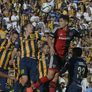 El delantero canalla Marco Ruben disputa una pelota con el defensor rojinegro Franco Escobar.