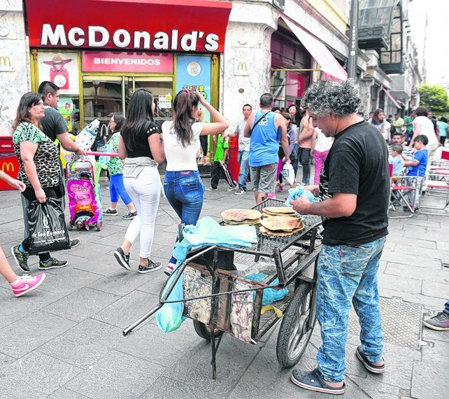 al paso. Un vendedor de torta asada se instaló a vender en el cruce de las peatonales con su parrilla