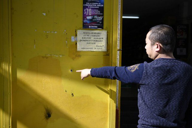 El propietario del local señala el agujero que provocó el proyectil de bala.