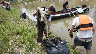 Los voluntarios retiran residuos del lecho del arroyo Ludueña.