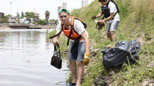 Un voluntario muestra una cartera de mujer extraída del arroyo Ludueña.