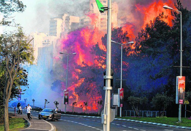 impactante. Peatones huyen de llamas de más de 15 metros de alto en un barrio de Haifa.