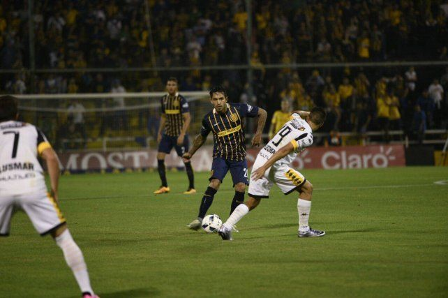 Gustavo Colman busca el pase ante la marca de un futbolista de Olimpo.
