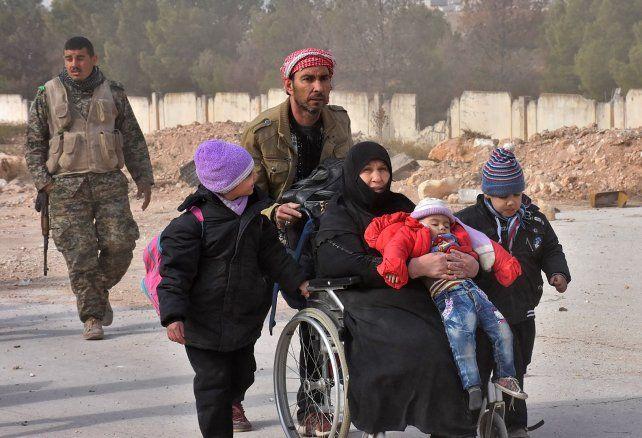 Desastre humanitario. Una familia siria es ayudada a abandonar Alepo.
