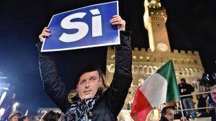 En juego. Una mujer con una máscara del primer ministro italiano hace campaña a favor del sí durante un acto de cierre en Florencia