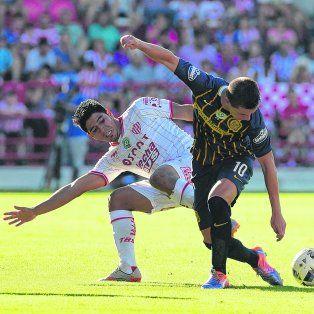 Pocos lujos. Lo Celso intenta maniobrar ante la marca de Diego Godoy en una de las pocas jugadas en las que participó. El volante canalla sólo mostró destellos de su talento.