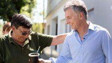 En Larroque, donde participó de un nuevo timbreo, el presidente Macri acepta el mate ofrecido por un vecino.
