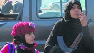 Evacuación. Una mujer con un fusil Kalashnikov llega con su hijo a Idlib.