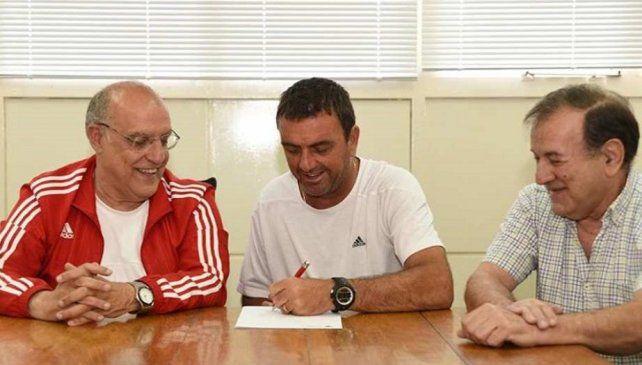 Todos contentos. Osella firma con la zurda el nuevo vínculo y se muestra feliz junto al presidente Bermúdez y el secretario Menchón.