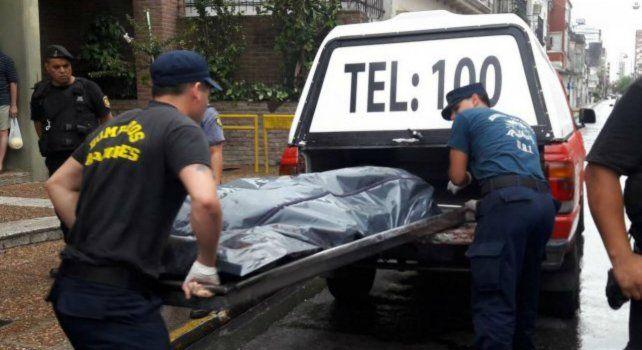 La policía traslada el cuerpo de una de las víctimas.