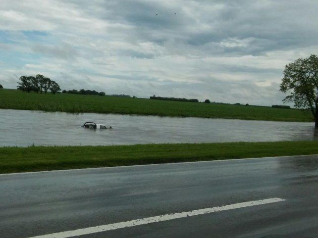 Un vehículo quedó sumergido en la banquina de la ruta 33. (foto vía Twitter:@RoloSanchez)