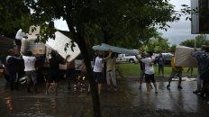 Los vecinos ayudan a descargar colchones para un centro de evacuados de Arroyo Seco.