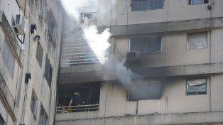 Los bomberos trabajan en el departamento 6 del piso 11 del edificio ubicado en Corrientes entre Pellegrini y Cochabamba.