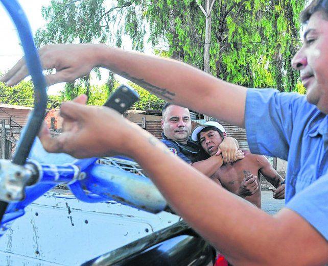 detención. Un policía detiene a un hombre que pasaba por el lugar en bicicleta. La policía insultó a la prensa.