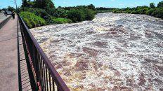amenaza. El agua baja con fuerza y la erosión de la cascada pone en riesgo la estabilidad del puente.