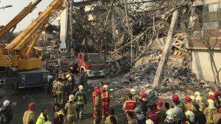 Bomberos de la capital iraní trabajan en el lugar donde colapsó el hotel