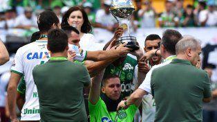 El arquero Jackson Follman, uno de los sobrevivientes de la tragedia, levanta la Copa Sudamericana que le cedió a Chapecoense el Atlético Nacional de Medellín.