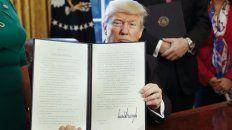 Mirada. El mandatario muestra el decreto al rubricarlo.