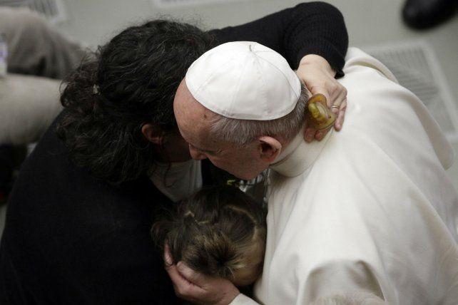 Afecto. Francisco abraza a una mujer y a su hija durante una audiencia.