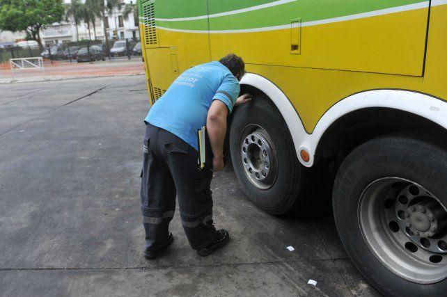 Uno de los agentes de la Comisión Nacional de Regulación del Transporte (CNRT) observa cubiertas en la estación de colectivos.