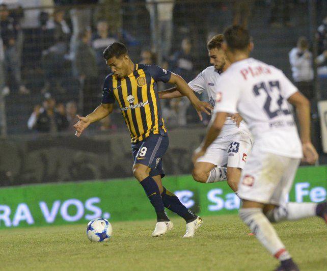 Teo Gutiérrez escapa con el balón ante dos defensores.