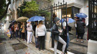 En el consulado italiano de Rosario es habitual ver cómo la gente forma fila a la intemperie para ingresar. incluso bajo la lluvia.