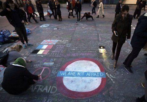 Angustia y dolor. Mujeres cubiertas con pañuelos escriben mensajes de solidaridad con los fallecidos.
