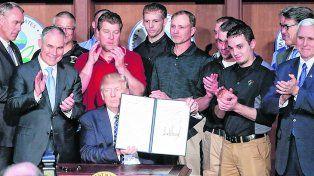 firmado. Trump, rodeado de su gabinete y empleados de una minera, exhibe el decreto de la polémica.