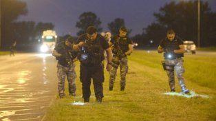 busqueda. Policías buscan rastros en el lugar del ataque en la autopista.