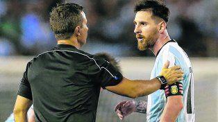 El eje de la discordia. Leo Messi dialoga con el asistente brasileño Emerson de Carvalho