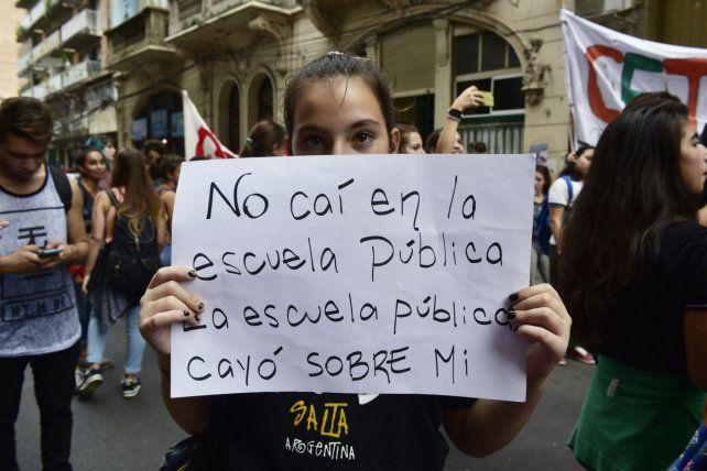 Claridad. Una alumna muestra un cartel que describe a la perfección el estado edilicio de la Nigelia Soria.