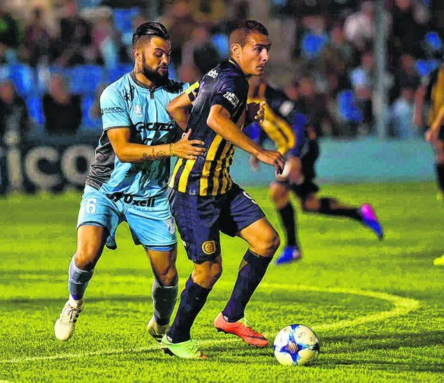 Pelota al pie. El capitán canalla controla el balón ante el acoso de Gastón Aguirre