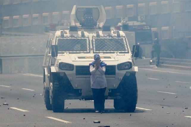 La impactante imagen de la mujer en medio de la marcha bloqueando el paso del vehículo.