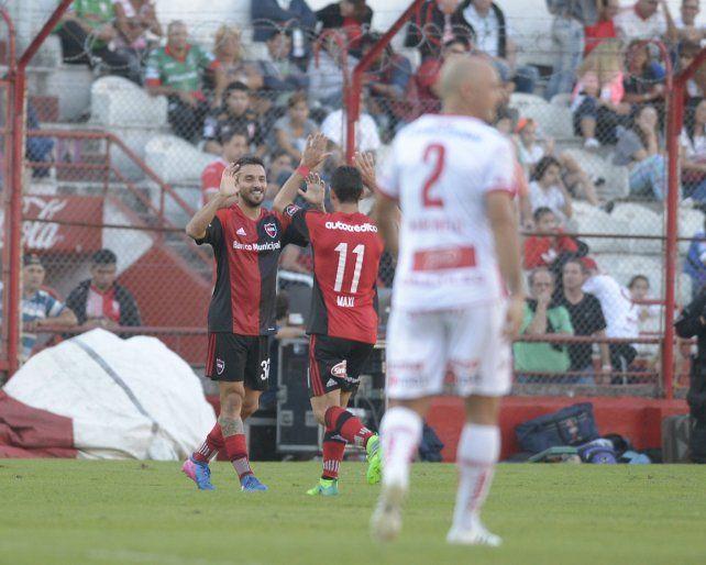 El goleador Nacho Scocco acaba de marcar el tanto de la victoria rojinegra y va a abrazarse con Maxi Rodríguez.