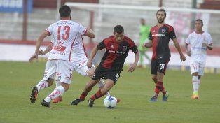 Jacobo Mansilla maniobra ante dos jugadores de Huracán.