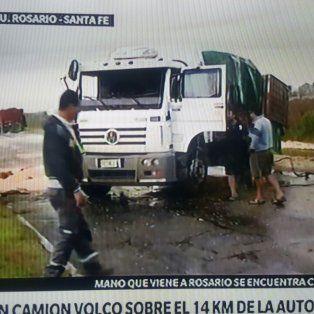 un camion con acoplado volco en la autopista y derramo soja en el pavimento