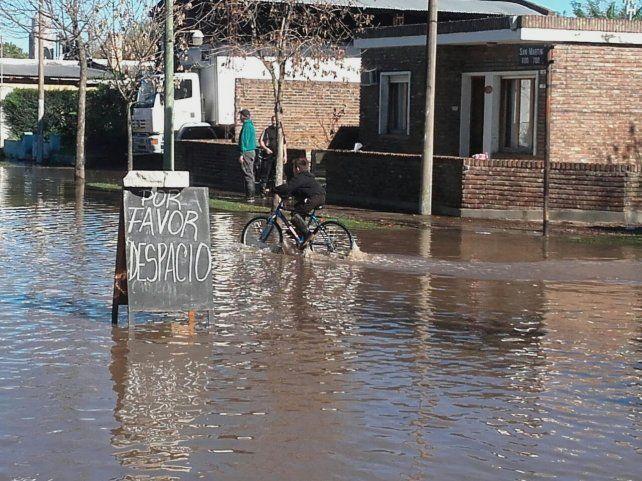 No hagan olas. Los habitantes intentan que el agua no ingrese en las viviendas y los comercios.
