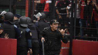 Un policía pide refuerzos para intentar controlar a los hinchas rojinegros.