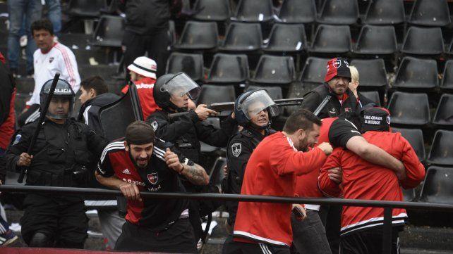 Un grupo de hinchas rojinegros intentan escapar de las balas policiales.