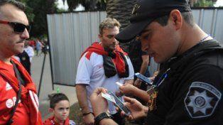 A presentar el DNI. Un oficial de la policía usa su celular para escanear el documento del hincha leproso en uno de los ingresos.