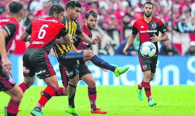 Calidad. Teo toca la pelota ante la marca de Domínguez y Sills.