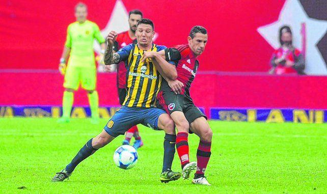 Presencia. Musto disputa el balón con vehemencia con Maxi Rodríguez. El casildense tuvo una gran actuación en el clásico.