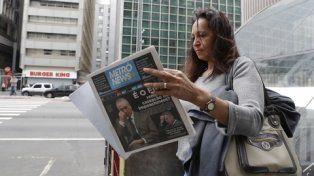 Conmoción. Una paulista lee las noticias sobre el escándalo de sobornos que complica al primer mandatario.