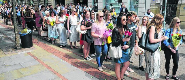 Homenaje póstumo. Británicos aguardan en fila para depositar flores por los 22 fallecidos en el atentado explosivo.